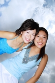 Two women smiling at camera, low angle view - Asia Images Group