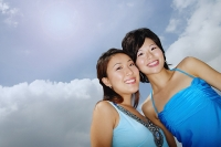Two women standing cheek to cheek, smiling at camera, low angle view - Asia Images Group