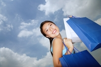 Young woman with shopping bags, smiling at camera, low angle view - Asia Images Group