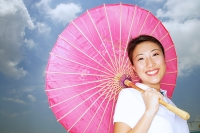 Young woman with pink umbrella, smiling at camera - Asia Images Group