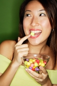 Woman with bowl of candy, putting candy into mouth - Asia Images Group