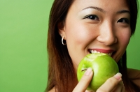 Woman eating green apple - Asia Images Group