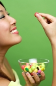 Woman holding single piece of candy and candy bowl - Asia Images Group