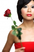 Woman holding single stalk of rose - Asia Images Group