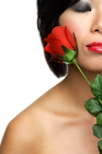 Woman holding rose, eyes closed - Asia Images Group