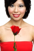 Woman holding rose, smiling at camera - Asia Images Group