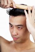 Man brushing hair - Asia Images Group