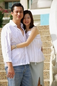 Couple standing, embracing, looking at camera - Asia Images Group