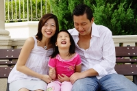 Family with one child, sitting on bench - Asia Images Group