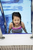 Girl in swimming pool, looking at camera - Asia Images Group