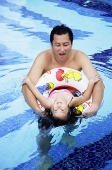 Father and daughter in swimming pool, daughter using inflatable ring - Asia Images Group