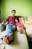 Father and daughter lying on sofa, smiling - Asia Images Group
