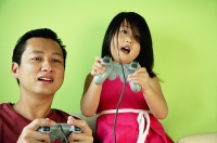 Father and daughter, side by side, playing video games - Asia Images Group