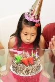 Girl blowing out birthday cake - Asia Images Group