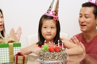 Girl with birthday cake, parents on either side clapping - Asia Images Group