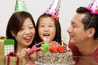 Girl with birthday cake, parents on either side smiling - Asia Images Group
