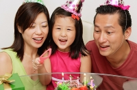 Family with one child celebrating a birthday - Asia Images Group