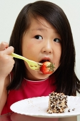 Young girl eating strawberry with fork - Asia Images Group