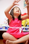 Young girl sitting cross-legged, looking up, hands raised - Asia Images Group