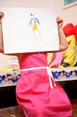 Young girl holding drawing over face - Asia Images Group