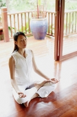 Woman practicing yoga, sitting in lotus position - Asia Images Group