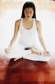 Woman practicing yoga, sitting in lotus position, eyes closed - Asia Images Group