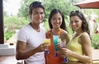 Young adults holding drinks looking at camera - Asia Images Group