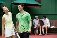 Couples spending time together on tennis court, laughing - Asia Images Group