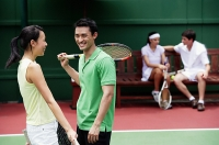 Couples at tennis court, talking - Asia Images Group