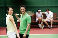 Couple at tennis court, looking at camera, smiling - Asia Images Group
