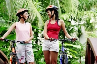 Two women standing with bicycles, smiling at each other - Asia Images Group