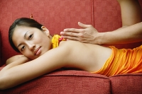 Woman lying on sofa getting a massage - Asia Images Group