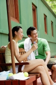 Couple in tennis outfit, sitting on bench on tennis court - Asia Images Group