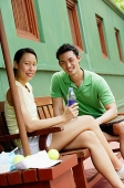 Couple sitting on bench on tennis court, smiling at camera, woman holding water bottle - Asia Images Group