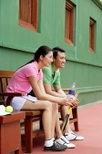 Couple sitting on bench, looking away, smiling - Asia Images Group