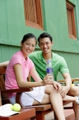 Man and woman sitting on bench, smiling at camera, woman with water bottle - Asia Images Group