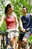 Couple with bikes, smiling at each other - Asia Images Group
