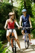 Couple wearing helmets, riding bikes, smiling - Asia Images Group