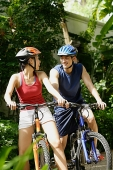 Couple riding bikes and smiling, looking at each other - Asia Images Group