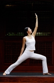 Woman stretching with one arm up in air, doing yoga pose - Asia Images Group