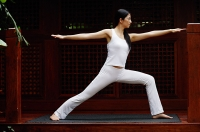 Woman doing a yoga pose with arms outstretched - Asia Images Group