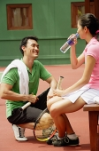 Couple at tennis court, drinking water - Asia Images Group