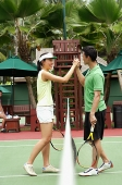 Man and woman giving high five across tennis net - Asia Images Group
