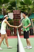 Man and woman shaking hands, tennis match - Asia Images Group