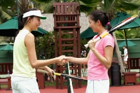 Two women shaking hands across tennis net - Asia Images Group