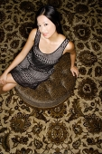Woman sitting on oriental carpet, looking at camera - Asia Images Group