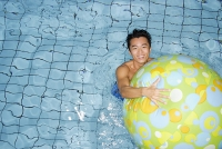 Man in swimming pool, holding on to beach ball - Asia Images Group
