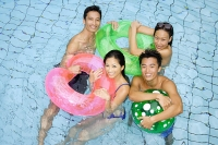 Couples in swimming pool with floats - Asia Images Group