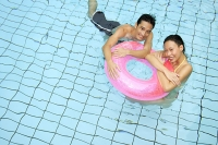 Couple in swimming pool leaning on inflatable ring, looking at camera - Asia Images Group