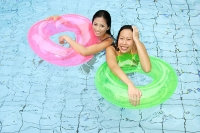 Women in swimming pool, holding inflatable ring, looking at camera - Asia Images Group